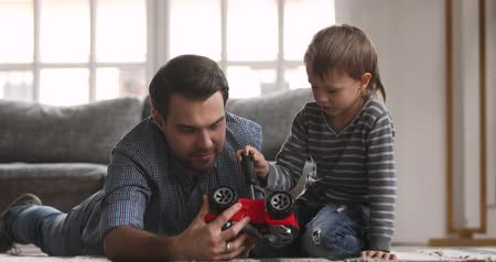 custodia : Young dad teaching focused cute little kid child son playing pretending repairing toy car holding screwdriver fixing truck having fun on floor in living room, family daddy child leisure game concept Filmati Stock