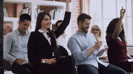 аудитория : Female training participant raise hand up ask question at conference workshop sit on chair with business audience group, businesswoman listen corporate lecture seminar, professional education concept
