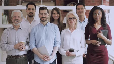 leden : Serious happy professional business team video portrait, young and old diverse leaders employees posing together standing in office, multiracial staff corporate people workers group looking at camera Stockvideo