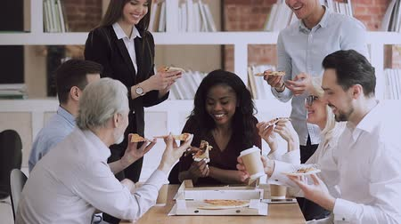 lunchen : Happy multiracial young and old friendly business team people have fun share pizza together in office, diverse workers staff group talk laugh eat lunch dinner enjoy corporate party sit at work table Stockvideo