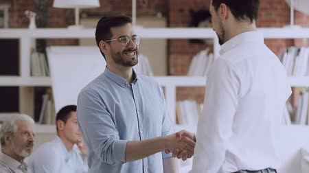 membro : Proud manager handshaking praising promoting male employee thanking for good work, happy businessman shake hand boss congratulating rewarding worker expressing trust, appreciation and respect concept