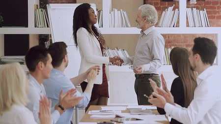 感謝 : Old senior manager leader handshaking promoting rewarding happy african american young female office worker, proud aged male boss and team congratulating black employee, recognition at work concept 動画素材