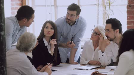 mentorat : Male leader business coach mentor teacher talking brainstorming new project at table, executive manager boss training employees group explaining work plan at diverse team staff corporate meeting