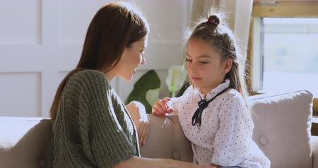 foster : Caring understanding young adult mum talking with little cute school child daughter sharing problems giving love help care sit on sofa at home, parent and kid trust conversation support concept Stock Footage