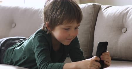 obsession : Curious cute schoolboy hold smartphone device watching social media videos alone at home, little preschool kid using mobile apps play games laying on couch, children obsessed with technology concept
