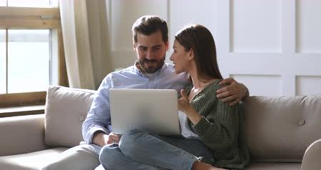 wyprzedaż : Happy husband and wife relaxing sitting on sofa enjoying using laptop computer, 30s young couple looking at notebook screen browsing internet choosing shopping online resting together in apartment