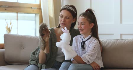 lalka : Happy young adult mother babysitter and cute schoolgirl daughter play hand puppet theater at home, beautiful mum wear crown having fun with small kid girl hold toys enjoy fairy tale game sit on sofa