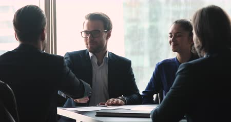 dankbaarheid : Happy corporate business group male partners shake hands at board meeting sit at office conference table, businessman company representative handshake client make partnership trust agreement concept Stockvideo