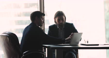 работодатель : Young businessman startupper wear suit showing presentation sell online startup project to business investor client explaining deal benefits pointing at laptop computer sit at office desk meeting