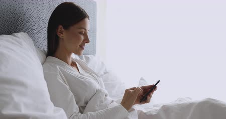 planlamacı : Happy young lady user holding cellphone texting message sit in cozy bed, smiling woman using smart phone apps in morning surfing checking social media buying choosing online in mobile application