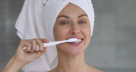 mindennapi : Beautiful young woman with towel on head hold toothbrush brushing healthy teeth look at camera, attractive lady cleaning mouth with toothpaste in bathroom, morning dental care concept, close up view