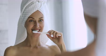 mindennapi : Happy beautiful young adult woman with towel on head hold toothbrush brushing healthy white teeth clean mouth with toothpaste doing dental care morning routine hygiene concept look in bathroom mirror