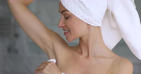 hyperhidrosis : Attractive happy young woman wrapped in towel hold apply antiperspirant in armpit, happy lady use deodorant stick in underarm, daily hygiene freshness hyperhidrosis treatment concept, close up view