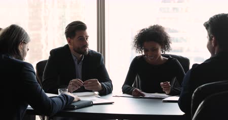 briefing : Male boss leader wear suit discuss project paperwork with multi ethnic team at meeting, confident businessman mentor ceo executive consult corporate diverse businesspeople group sit at meeting table Stock Footage