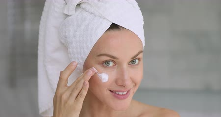 mindennapi : Beautiful young woman applying moisturizing day facial creme looking at camera, happy lady wrap towel on head putting lifting anti aging cream hydrating dry face skin care concept, close up portrait