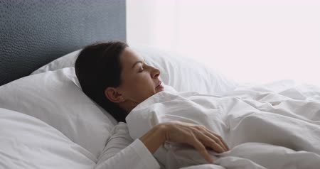wakeup : Sick upset young woman wear pajama waking up sit in bed touching aching back feel backpain pain morning discomfort low lumbar problem after bad sleep on uncomfortable mattress, backache concept Stock Footage