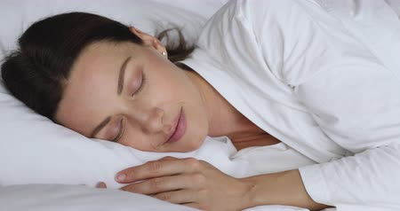 bastante : Calm serene young beautiful woman wear pajama resting in comfortable white bed, peaceful healthy 30s lady attractive face lying asleep on soft pillow orthopedic mattress enjoying good sleep concept
