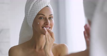 krem : Funny happy attractive woman apply skincare cream on face look in bathroom mirror, healthy young lady wrap towel on head put moisturizing lifting facial creme, healthy skin care treatment concept Stok Video