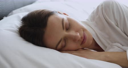 белье : Healthy attractive lady sleeping with eyes closed relax in bed, peaceful serene young woman beautiful face wear pajama lying asleep resting in cozy white bed enjoy good sleep concept, close up view