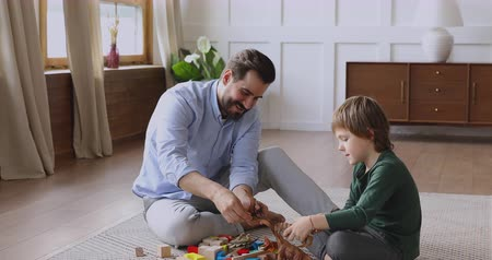 vazba : Loving young dad and cute small child son playing with dinosaurs and wooden blocks sit on carpet floor, happy single parent adult father enjoy helping little kid hold toys having fun at home together Dostupné videozáznamy
