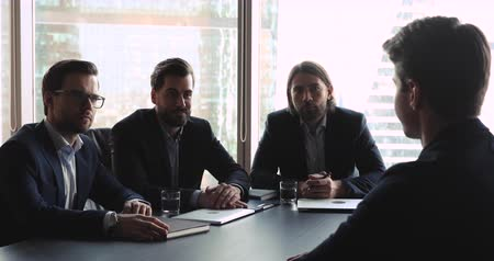 kandidát : Company employers group wear suits discuss work experience ask questions listening male seeker at job interview meeting sit at table, corporate recruitment, hiring and professional employment concept