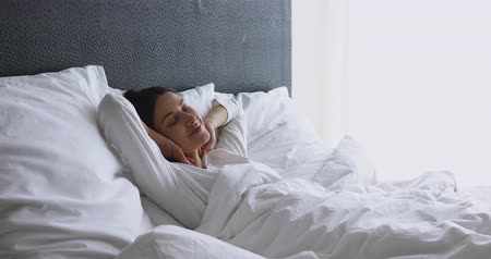 wakeup : Happy healthy young adult woman waking up on early pleasant lazy weekend lying in cozy bed on soft pillow orthopedic mattress stretching raising arms enjoy good morning concept feel fresh and rested