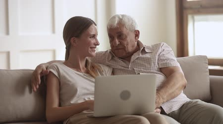 представитель старшего поколения : Happy senior retired father embracing adult daughter using laptop at home, old elder dad hug young grown woman talking laughing look at computer sit on sofa, two age generation bonding with device