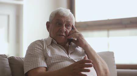 hívó : Happy elder senior man holding cellphone talking on phone at home, smiling older retired mature grandfather making call enjoy mobile telecommunication laughing speaking by smartphone sit on sofa