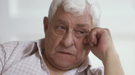 luto : Upset depressed older elder gray-haired man crying wiping tear sit alone at home, sad stressed poor senior grandfather widower feel sorrow grief suffer from loneliness concept grieving, close up view Stock Footage