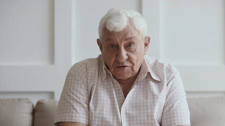 facetime : Happy senior elder man looking talking to camera recording vlog or making skype call at home, old grey-haired aged grandfather doing video chat or shooting footage for youtube channel, webcam view Stock Footage