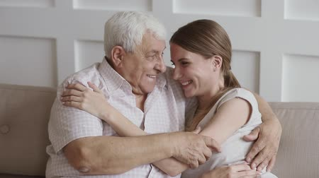 home grown : Close up portrait of happy two generation family senior old father and young adult daughter embrace bonding looking at camera, smiling grandfather hug grown granddaughter cuddling together at home Stock Footage