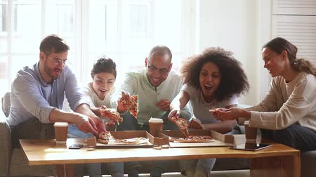 etnia africano : Happy diverse friends group having fun eating pizza together share dinner meal at home or in dorm, multicultural hungry young people students laughing talking during lunch food at party meeting Stock Footage