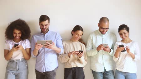 bağımlılık : Multiracial smiling young people group using gadgets stand in row against wall, happy diverse female male users obsessed with modern technology devices holding phones tablet, tech addiction concept Stok Video