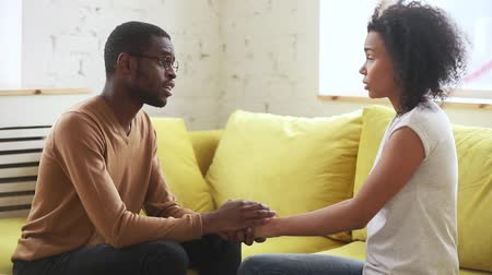 sorry : Young african american husband feeling guilt apologizing talking begging upset wife ask for forgiveness, black man holding hand of sad woman saying sorry please forgive get rejection sitting on sofa