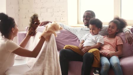 poppetjes : Happy african father and kids enjoying watching mom puppet show sit on sofa, loving mother playing marionette toys do theatre performance for cute children at home, creative family leisure activity