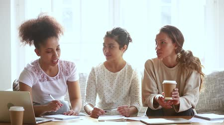 bijles : Three mixed ethnicity girls students talking studying together at home, african indian and caucasian friends discussing project assignment working in teamwork learning helping preparing for test exam