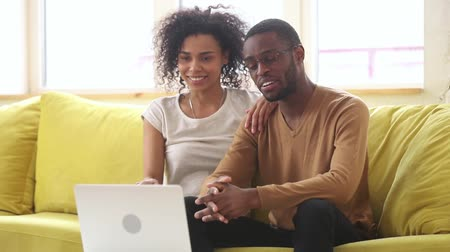 conferencing : Happy african american young couple waving hands talking to webcam making video call on skype, smiling black man and woman looking at laptop screen enjoy online conversation sitting on sofa at home
