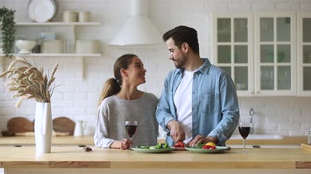 adega : Happy young family couple enjoy cooking talking together in kitchen, husband cut healthy vegetable salad chatting with smiling wife food wine on table prepare healthy meal on romantic dinner at home