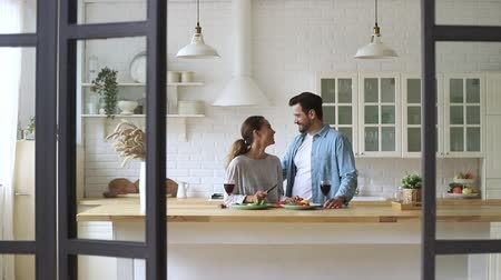 adega : Happy loving young family couple cutting fresh vegetable salad having fun cooking together in modern cozy kitchen interior, smiling husband and wife bonding laughing helping prepare healthy meal Vídeos