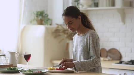 gevşek : Happy young woman holding knife cutting fresh organic vegetables for salad in kitchen, smiling fit vegetarian girl prepare healthy dinner make surprise for husband enjoy glass of wine cooking at home