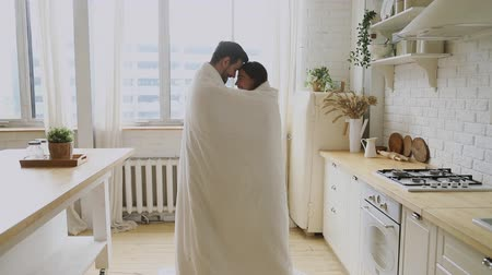 клетчатый : Happy affectionate romantic young couple standing in kitchen room wrapped with warm blanket enjoy bonding talking in cozy morning at home, loving husband and wife laugh having fun covered with plaid