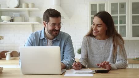 kitchen paper : Happy young husband and wife using calculator laptop computer talking doing paperwork together sit at kitchen table discussing family mortgage loan payments pay bills manage finances expenses at home