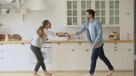 ипотека : Happy funky young romantic couple dancing jumping listen music in kitchen, carefree active funny husband and wife first time home buyers having fun laughing celebrating buying new house freedom party