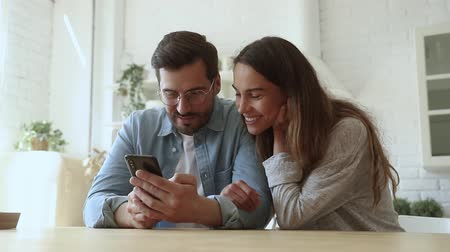 bağımlılık : Happy young couple using smartphone play mobile game or shopping in ecommerce app talking laughing, man and woman customers holding phone check social media application looking at cellphone together Stok Video