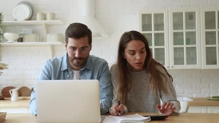 refund : Serious young couple husband and wife pay bills online on website app doing paperwork planning budget discuss finances calculate mortgage payments using laptop computer sit at kitchen table at home