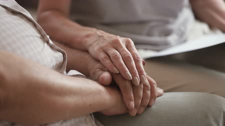 gekreukt papier : Close up middle aged woman stroking wrinkled hand of older male pensioner, sitting together on couch at home. Mature wife comforting retired husband, showing love. Healthcare, nursing concept.