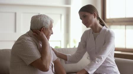 complaints : Pleasant young female general practitioner visiting old retired patient at home, stroking arms, listening to complaints. Smiling doctor comforting pensioner during checkup, giving psychological help. Stock Footage