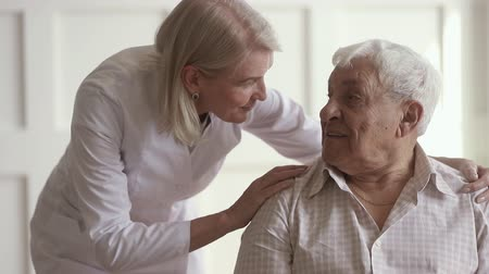 talk : Pleasant friendly middle aged nurse embracing shoulders of 80s male pensioner. Smiling female general practitioner comforting communicating with happy retired patient, asking about health condition.