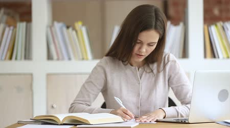 értékelés : Focused young female teen student reading textbook, making notes in copybook. Concentrated millennial girl studying in library classroom, preparing for evaluation examination, writing essay summary.