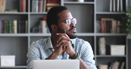 decidir : Thoughtful serious young african american man student writer sit at home office desk with laptop thinking of inspiration search problem solution ideas lost in thoughts concept dreaming looking away